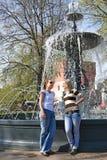 Due amici che chiacchierano allegro alla fontana della città immagini stock libere da diritti
