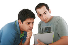 Due amici che esaminano sorpresi il calcolatore del ridurre in pani Fotografie Stock Libere da Diritti