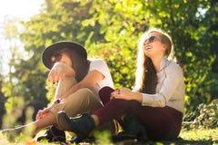 Due amici che godono del giorno di autunno nel parco fotografia stock