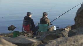 Due amici che pescano per sfuggire alla vita di città sollecitata, interessi comuni, tempo libero stock footage