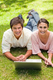 Due amici che ridono mentre guardando avanti come utilizzano un computer portatile Immagine Stock