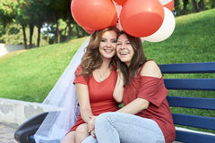 Due amici che si siedono sul banco con le palle fotografia stock