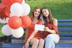 Due amici che si siedono sul banco con le palle immagine stock