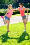 Due amici che si sostengono per le pose di yoga Fotografia Stock