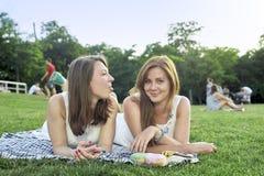 Due amici che si trovano sull'erba nel parco fotografie stock