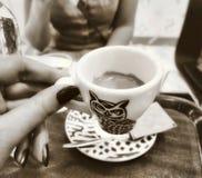 Due amici delle donne che bevono il caffè di marrone scuro all'interno comperano caffè Fotografie Stock Libere da Diritti