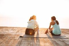 Due amici delle donne di sport all'aperto sulla conversazione di seduta della spiaggia a vicenda immagine stock