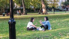Due amici delle donne mangiano e chiacchierano su prato inglese in Russell Square, Londra fotografia stock