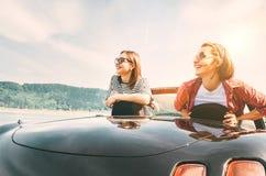 Due amici delle femmine che viaggiano in cabriolet, hanno un freno di arresto per godere dei landsxapes di una montagna immagini stock libere da diritti