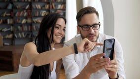 Due amici di lavoro scelgono le foto per i media sociali stock footage
