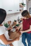 Due amici di ragazze che preparano cena in cucina che cucina insalata immagini stock libere da diritti