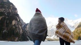 Due amici di viaggio delle giovani donne coperti nelle coperte che camminano al lago congelato video d archivio