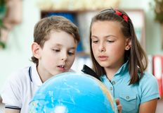Due amici esaminano un globo del banco Immagine Stock