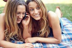 Due amici felici delle donne che dividono media sociali in a fotografia stock