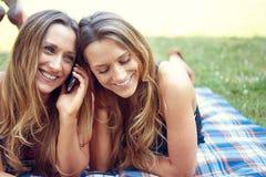 Due amici felici delle donne che dividono media sociali in a fotografie stock