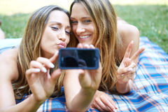 Due amici felici delle donne che dividono media sociali immagini stock libere da diritti