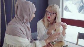 Due amici femminili adulti sono chiacchieranti e beventi il tè caldo nella casa nel giorno di inverno stock footage