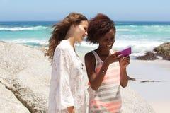 Due amici femminili alla spiaggia che esamina telefono cellulare Fotografia Stock