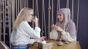 Due amici femminili alla tavola con le tazze di tè archivi video