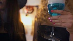 Due amici femminili che godono di Halloween fanno festa, tenendo i vetri con pozione blu video d archivio
