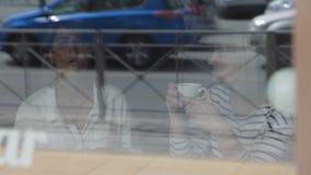 Due amici femminili che godono insieme del caffè stock footage