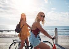 Due amici femminili che guidano le loro biciclette lungo la passeggiata della spiaggia Immagine Stock