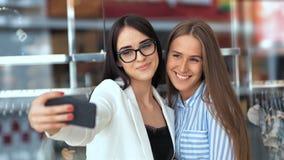 Due amici femminili di bellezza che fanno una certa spesa nel centro commerciale moderno e che prendono un selfie con uno smartph archivi video
