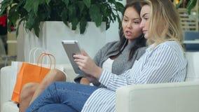 Due amici femminili divertendosi mentre comperando in un centro commerciale, avendo una rottura, facendo uso della compressa digi stock footage