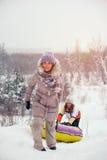 Due amici femminili divertendosi sulla collina della neve fotografia stock