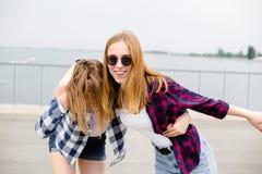 Due amici femminili sorridenti che si abbracciano sulla via Concetto di feste, di vacanza, di amore e di amicizia fotografia stock libera da diritti