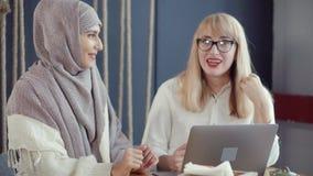 Due amici femminili stanno chiacchierando in caffè e stanno guardando su esposizione del computer portatile stock footage