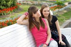 Due amici femminili sul banco Immagine Stock