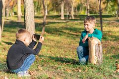 Due amici, i fratelli sono fotografati sul telefono nel parco un giorno soleggiato fotografie stock libere da diritti