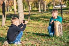 Due amici, i fratelli sono fotografati sul telefono nel parco un giorno soleggiato fotografia stock libera da diritti