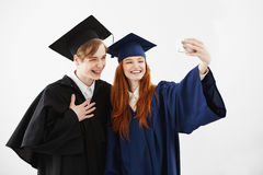 Due amici laureati in cappucci e manti che ridono facendo selfie sopra fondo bianco prima della ricezione del loro magister Fotografia Stock Libera da Diritti