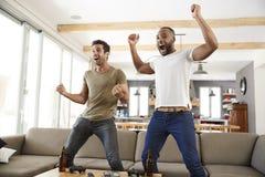 Due amici maschii eccitati celebrano gli sport di sorveglianza sulla televisione immagine stock