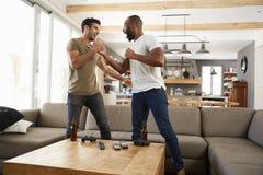 Due amici maschii eccitati celebrano gli sport di sorveglianza sulla televisione immagini stock