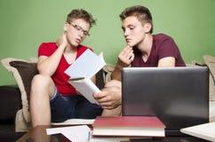 Due amici messi a fuoco mentre studiando fotografia stock