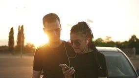 Due amici o coppie alla moda in magliette nere che stanno su una zona di parcheggio e che si divertono insieme mentre ascoltando video d archivio