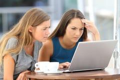 Due amici preoccupati che guardano il contenuto di media sulla linea Immagine Stock Libera da Diritti