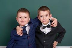 Due amici, ragazzo della scuola elementare vicino al fondo in bianco della lavagna, vestito in vestito nero classico, allievo del Fotografia Stock Libera da Diritti