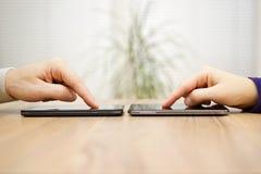 Due amici sono colleganti e dividenti gli archivi sopra gli Smart Phone Fotografia Stock