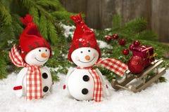 Due amici sorridenti dei pupazzi di neve nella neve Immagini Stock