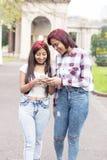 Due amici sorridenti della donna che per mezzo dello Smart Phone fotografia stock