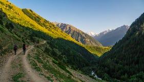 Due amici stanno facendo un'escursione nelle montagne di Caucaso Pista a Elbrus - il più alta montagna in Europa Immagine Stock Libera da Diritti