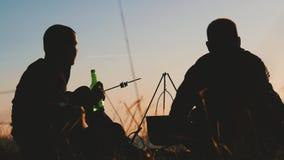 Due amici turistici felici che si siedono e che riscaldano vicino ad un fuoco di accampamento nella foresta al tramonto Il viaggi video d archivio
