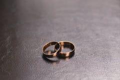Due ampie fedi nuziali dell'oro, posizionate su una superficie di cuoio marrone fotografia stock