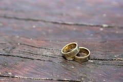 Due anelli del weddin dell'oro sulla tavola di legno Fotografia Stock