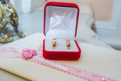 Due anelli di oro di nozze con i diamanti sono in una scatola rossa Immagini Stock