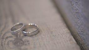 Due anelli dorati bianchi sul tiro di foto sulla tavola di legno all'aperto stock footage